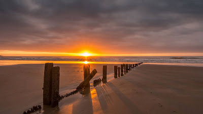 Wallpaper free sunset, sea, beach, wooden columns, sand+ Download Wallpapers